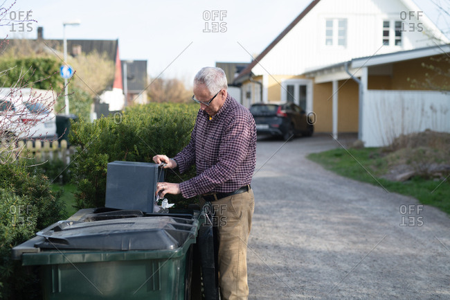 Elderly man emptying trash can into large waste container in driveway