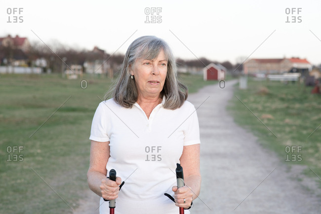 Portrait of active senior woman holding walking with poles for exercise