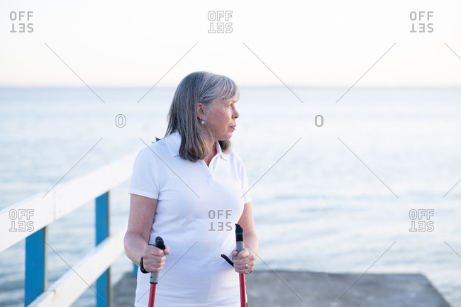 Close up of senior woman looking out at sunrise holding walking poles with sea in background