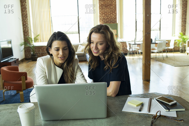 Businesswomen brainstorming at computer in office