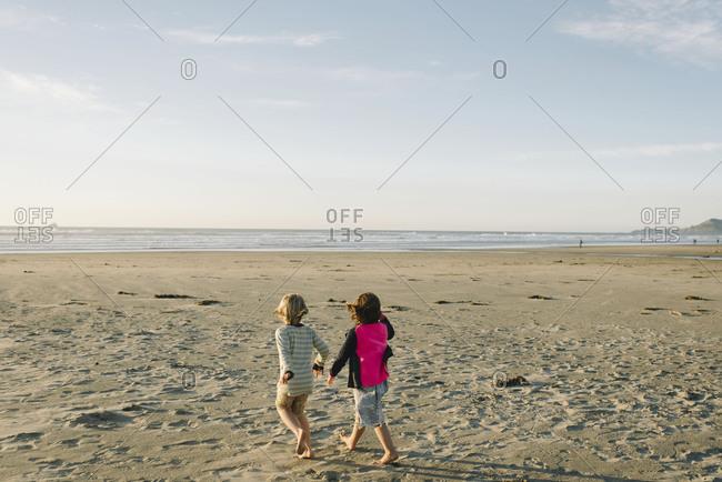 Girls walking towards ocean shore on sunny day