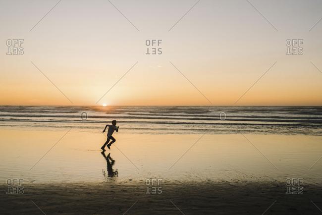 Young boy sprinting across wet sandy beach at golden hour