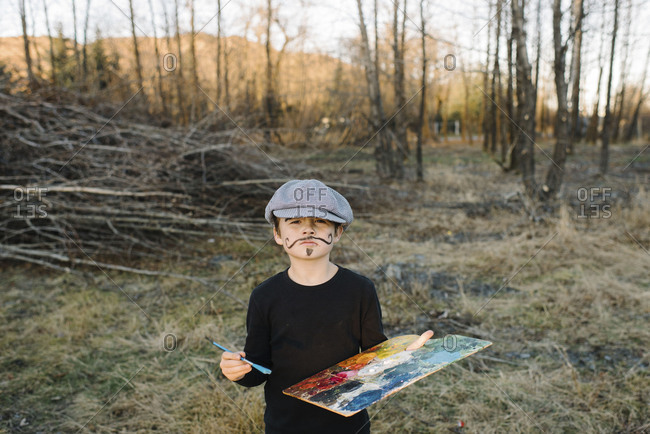 Boy posing in painter costume in backyard