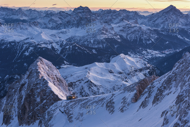 Sunrise from Punta Penia, the highest peak of Dolomites, in the Marmolada mountain group with Serauta hut lighting, Italy