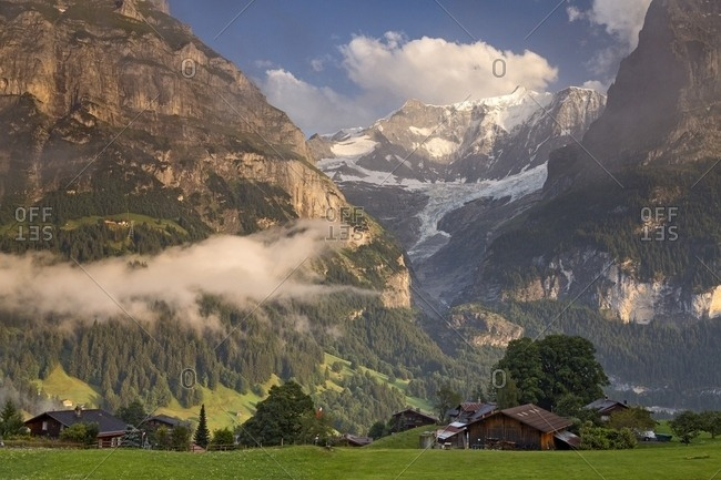 Sunset on Eiger and Fiescherhorn mountain, in foreground typical houses of Grindelwald, Berner Oberland, Switzerland, Europe