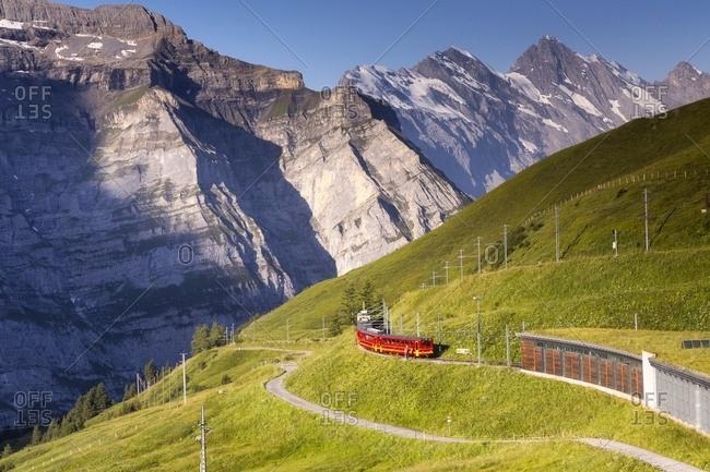 August 5, 2013: Typical swiss red train near Kleine Scheidegg station, Jungfraujoch Railway, Grindelwald, Switzerland, Europe