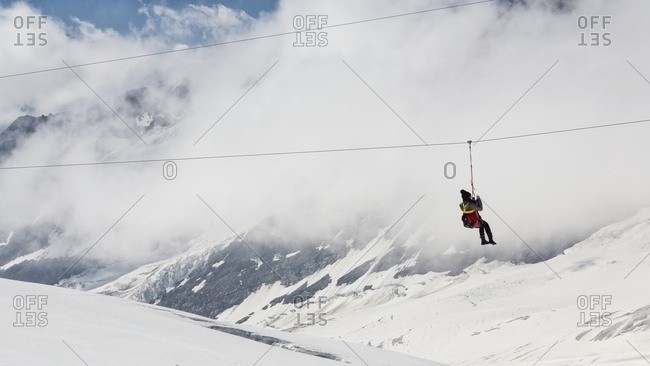 Tourist has fun on the Aletsch glacier, floating on the steel cable over crevasses, Jungfraujoch, Berner Oberland, Switzerland, Europe