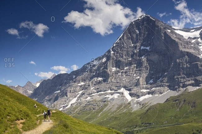 Hikers along the path from Mannlichen to Kleine Scheidegg, in front of famous north face of Eiger mount, Grindelwald, Berner Oberland, Switzerland, Europe