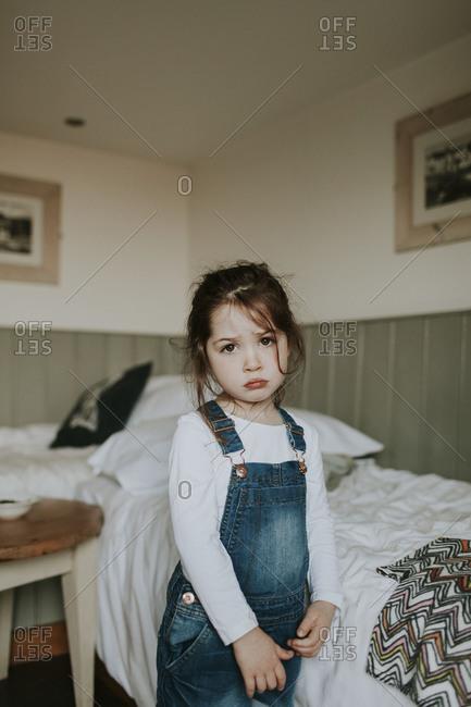 Forlorn toddler in overalls alone in bedroom