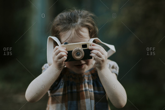 Girl pretending to take a photo with vintage camera toy