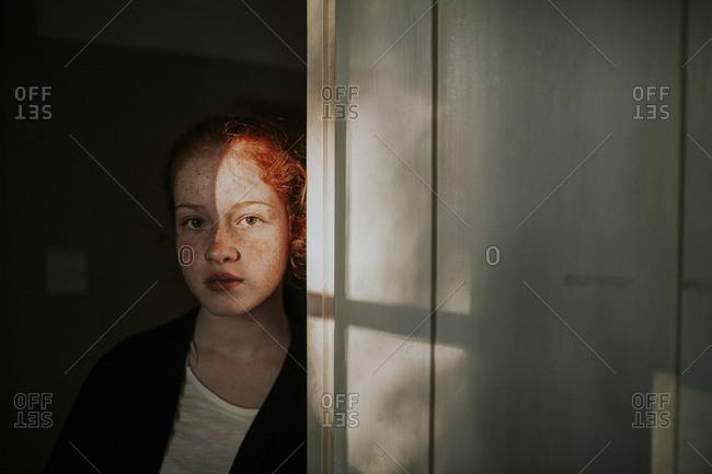 Serious preteen standing in shadowy doorway