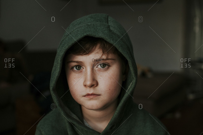 Solemn boy sitting alone with hoodie over head