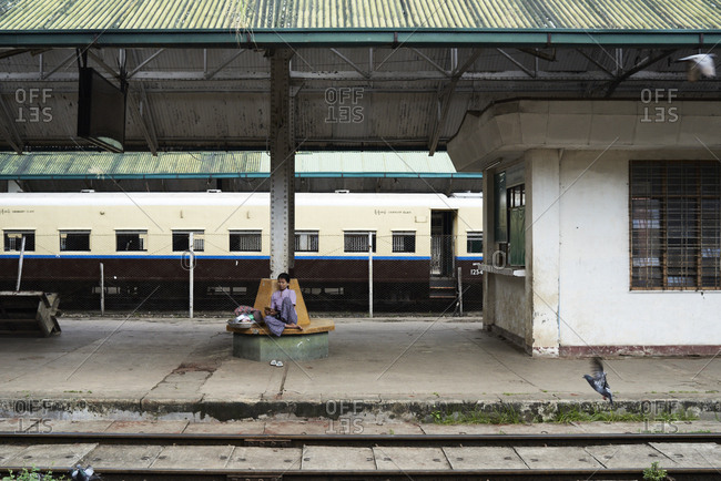 Yangon, Myanmar - October 28, 2017: Burmese lady sitting on a bench on a train station and using cell phone.