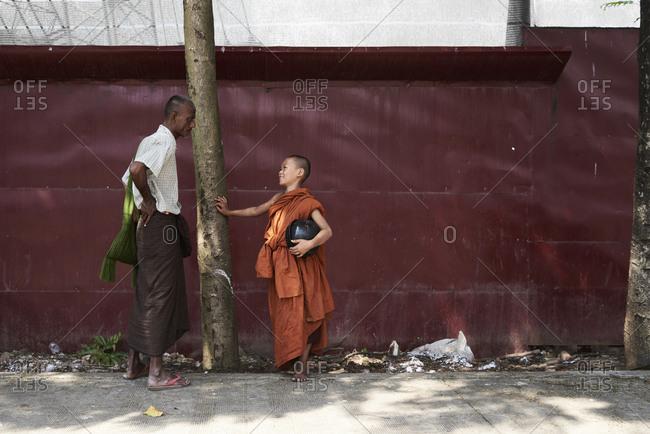 Yangon, Myanmar - October 27, 2017: novice monk talking smiley to his dad on the street.