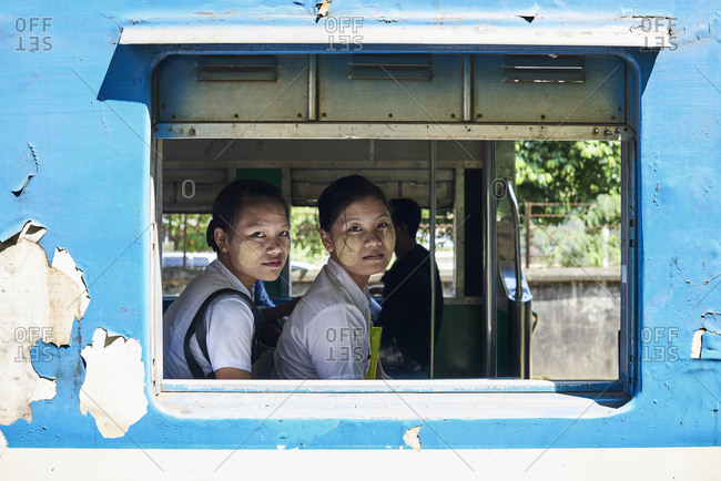 Yangon, Myanmar - October 27, 2017: Two young nurse students looking through the train window.