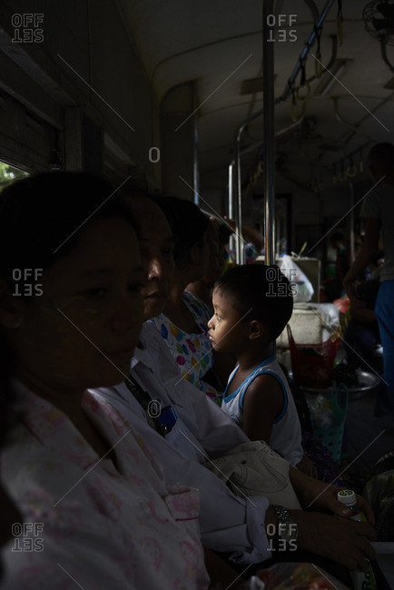 Yangon, Myanmar - October 27, 2017: Frozen moment of a burmese kid looking away surrounded by women inside of a train.