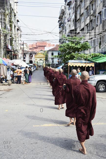 Yangon, Myanmar - October 28, 2017: Row of group of novice monks walking on the way to the monastery.