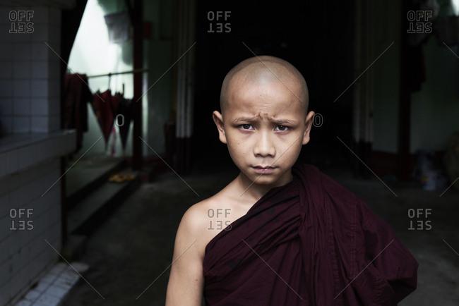 Yangon, Myanmar - October 28, 2017: Portrait of a bald novice monk outside monastery wearing traditional clothes.