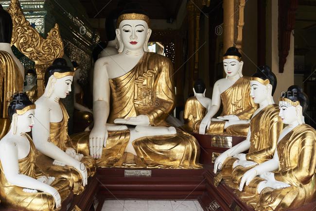 Buddha statues bathed in gold in Shwedagon Pagoda. Yangon, Myanmar.