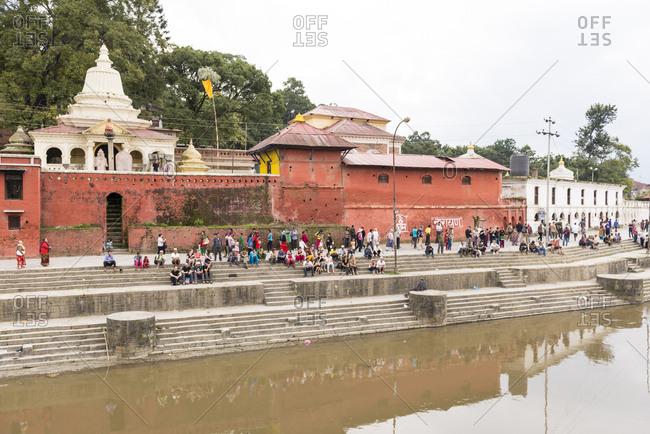Kathmandu, Nepal - May 10, 2012: People gathered on steps at the Pashupatinath Temple, Nepal