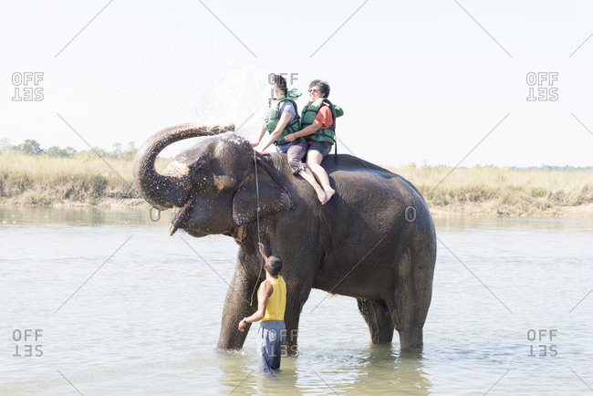 Nepal - June 8, 2012: Tourists being sprayed by an elephant, Chitwan National Park, Nepal