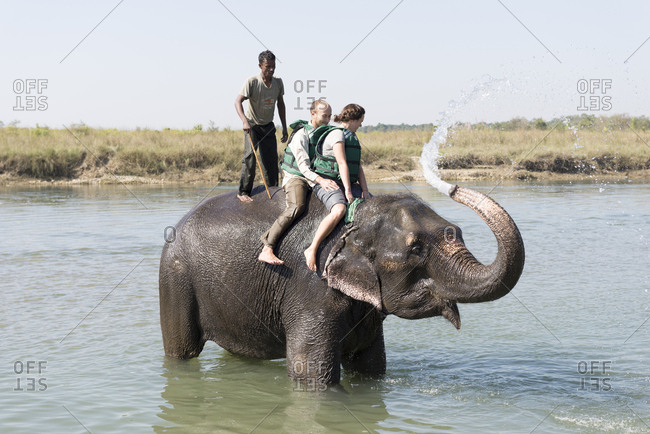 Nepal - June 8, 2012: Tourists being sprayed by an elephant in a river, Chitwan National Park, Nepal