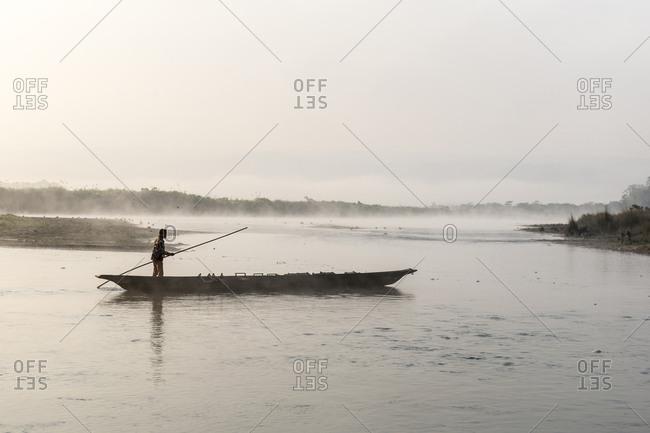 Nepal - June 12, 2012: Man on canoe in river at Chitwan National Park, Nepal