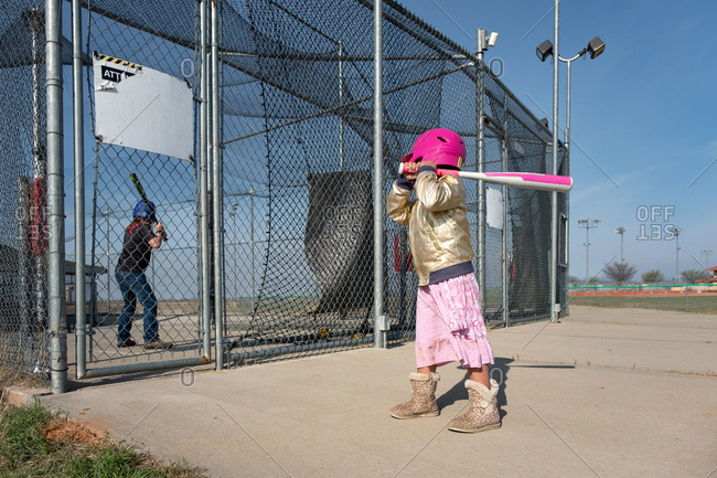 Little girl holding baseball bat at batting cages