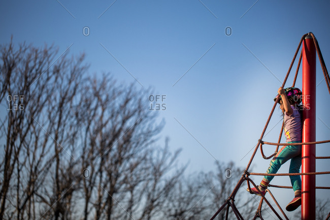 Little girl climbing on playground ropes