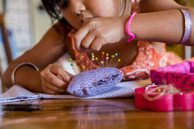 Little girl putting pins in a pincushion