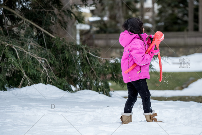 Little girl walking in snow with a snowball maker