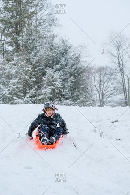 Boy sledding down snowy hill