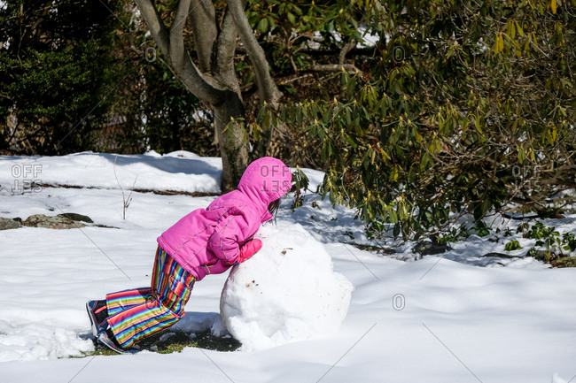 Little girl pushing large snowball for snowball