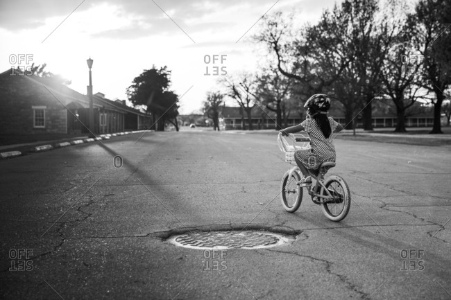 Young girl riding bike in black and white