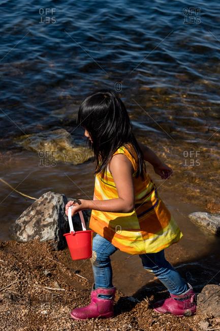 Little girl with bucket on lakeshore