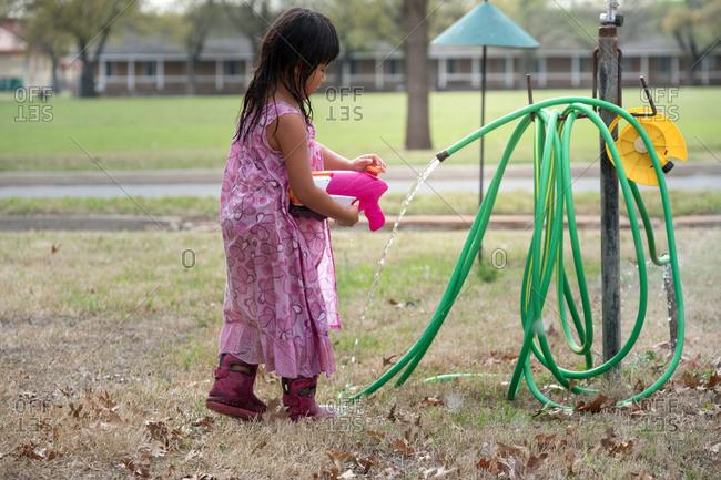 Young girl filling a water gun