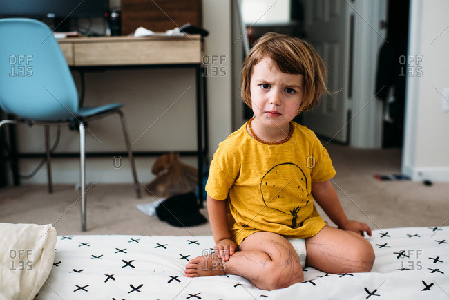 Toddler making an angry face stock photo - OFFSET