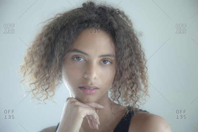 Portrait of a young woman with curly hair and hand on chin