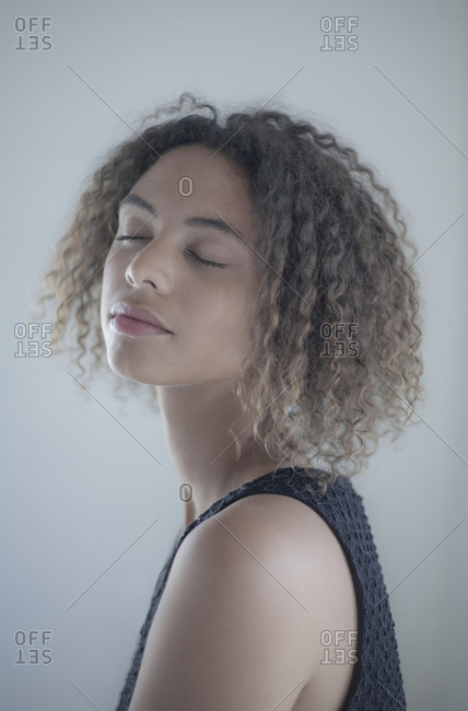 Portrait of young woman with curly hair and closed eyes