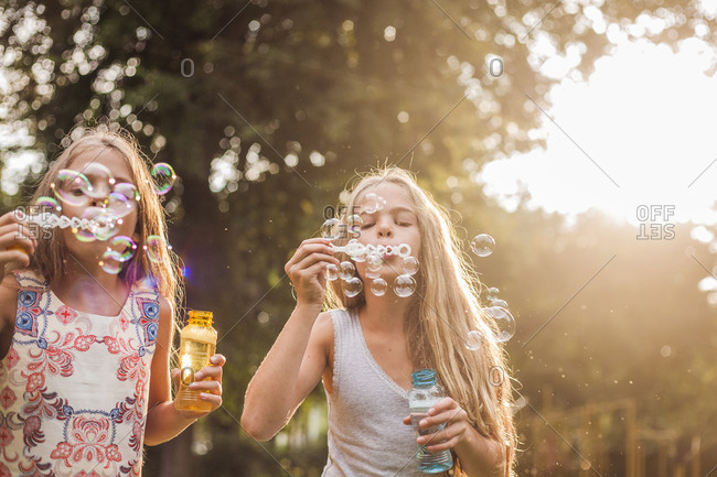 Girls blowing bubbles together in the park