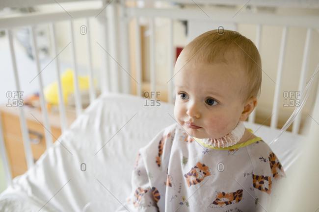 Cute sick baby boy sitting in hospital crib
