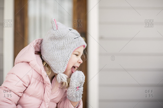 Playful girl licking snow from glove on porch