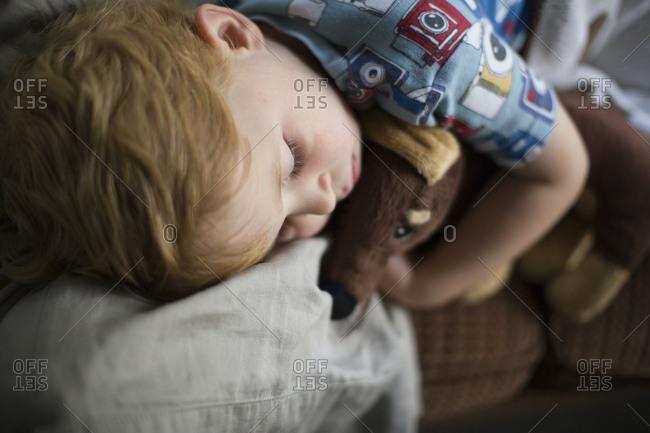Boy with teddy bear sleeping on sofa at home