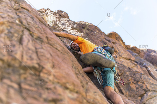 Low angle view of hiker climbing mountain