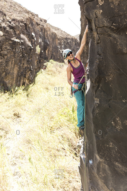 Full length of cheerful female hiker wearing helmet while climbing on mountain