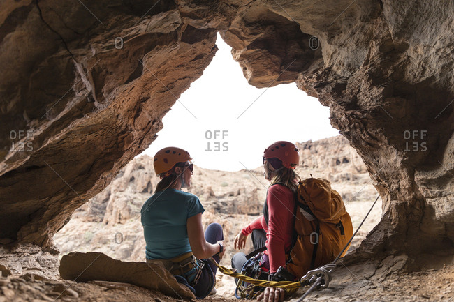 Female hikers sitting on entrance of cave in rock formation