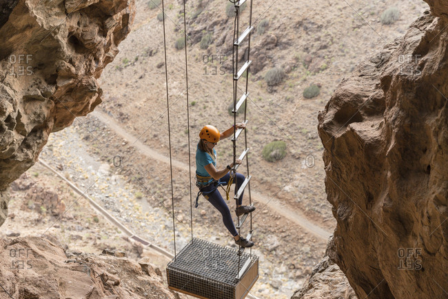 High angle view of female hiker climbing on rope ladder amidst mountains