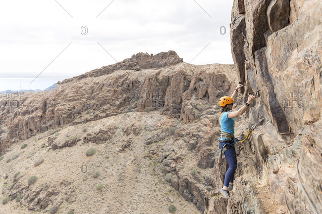 Female hiker using rungs while climbing on rock formation