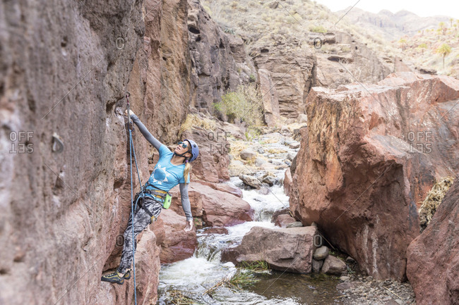 Female hiker using rope while climbing on rock formation by river