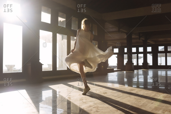Full length of young woman dancing on tiled floor during sunny day